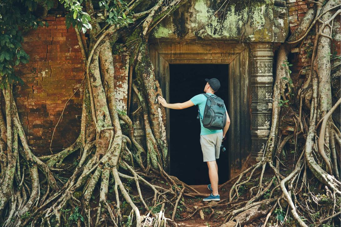 A Backpack University student exploring the Angkor Wat by stepping through a creepy doorway